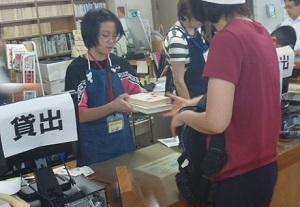貸出カウンターで両手で持った本を利用者に渡している様子