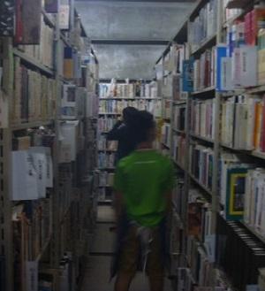 薄暗く、高い所まで本が並んでいる書庫を見学している様子